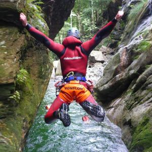A canyoner jumping in the water