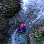 A canyoner sliding in a waterfall