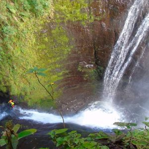 A canyoner walking in the water under a very big waterfall