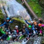 A group of canyoners posing for a photo near a waterfall