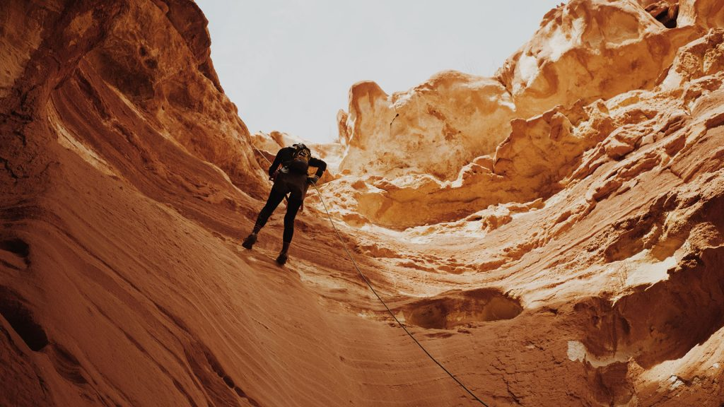 Abseiling a dry canyon by the use of a descender