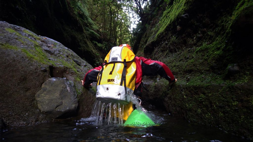 A canyoner with a canyoning backpack draining out water