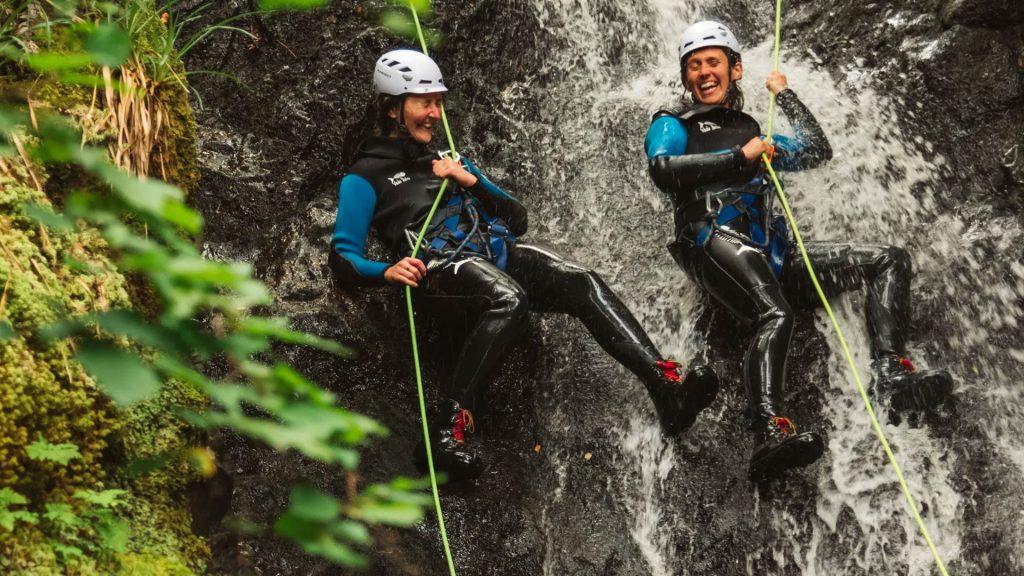 Two canyoners having fun abseiling a waterfall