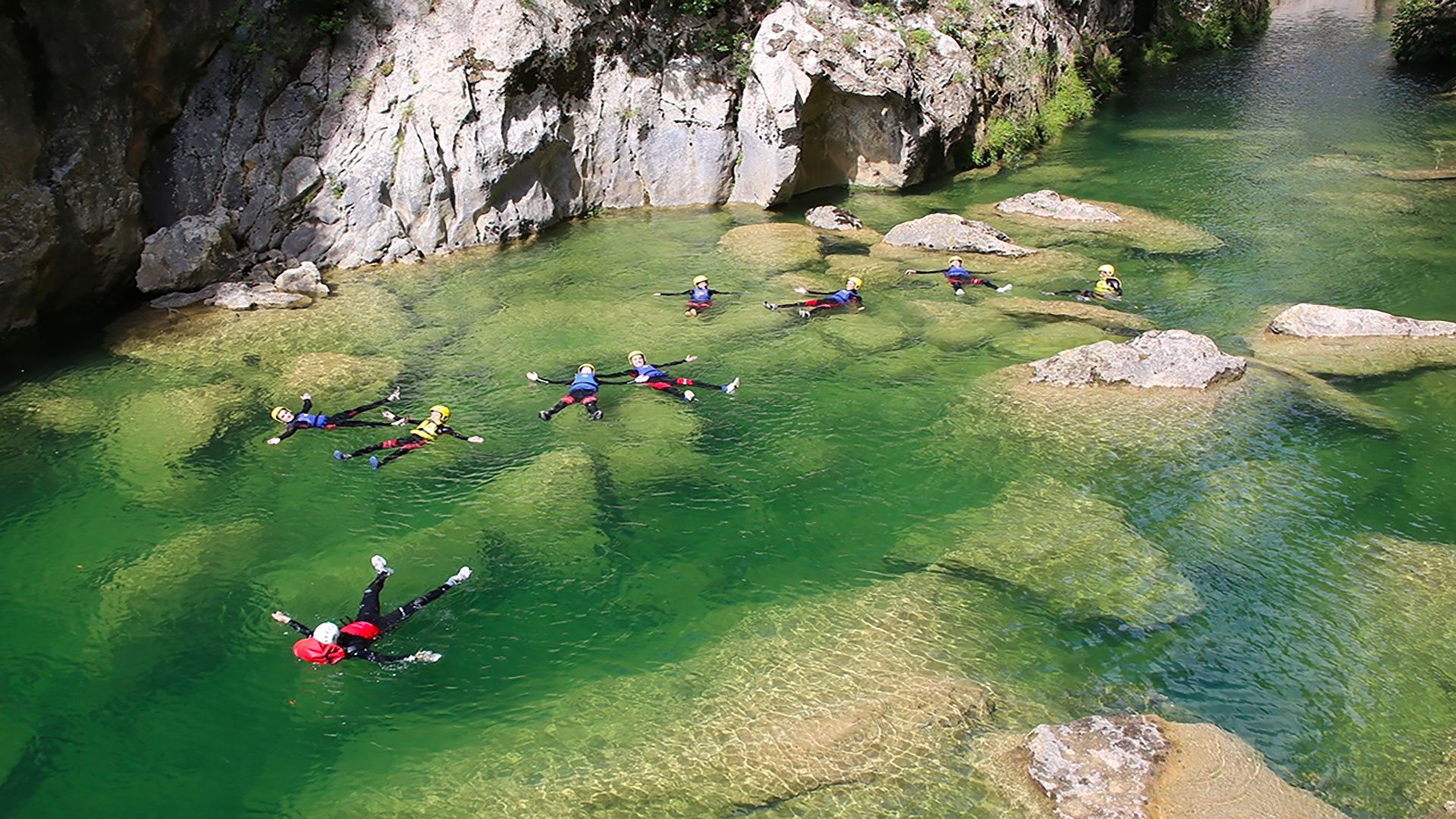 Canyoners swimming in a river during canyoning