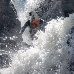 A canyoner abseiling a fully powerful waterfall